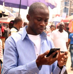 A mobile phone users seen checking his phone at the Ikeja Computer Village
