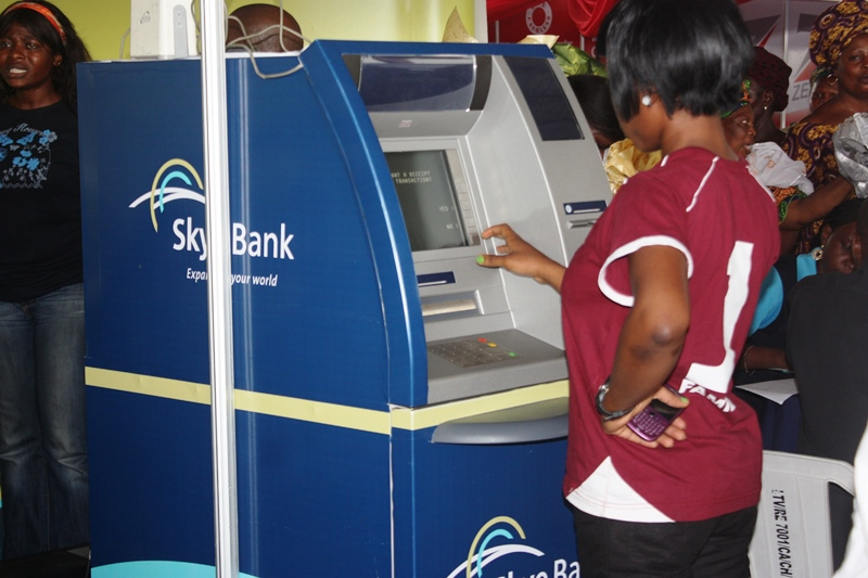 A bank staff seen using an ATM at an exhibition showcasing banking technologies and services in Lagos
