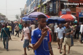 Technology Times file photo shows a young man seen using a mobile phone walking inside Computer Village in Ikeja, Lagos.