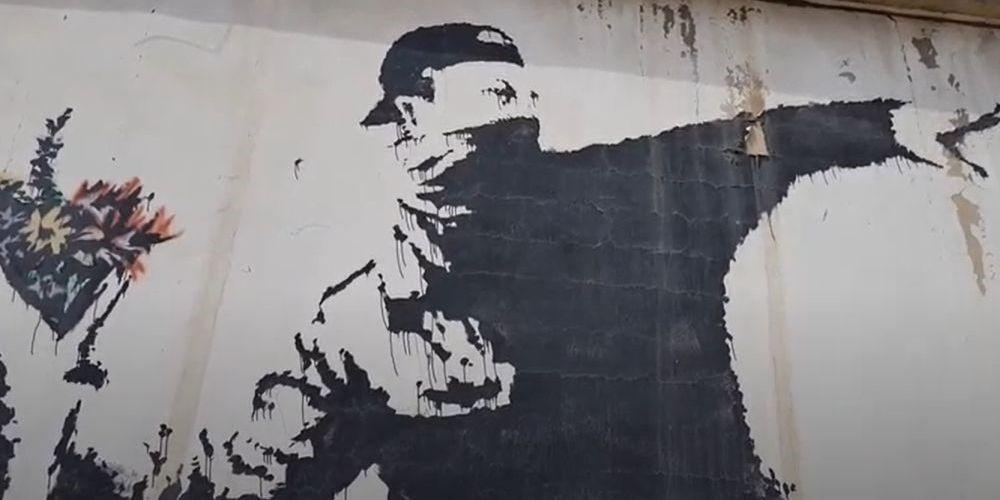 Le célèbre graffiti « Le lanceur de fleurs » de Banksy.