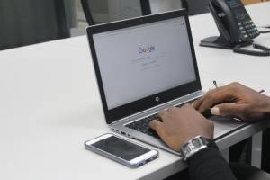 Un homme noir sur un ordinateur affichant une page Google.