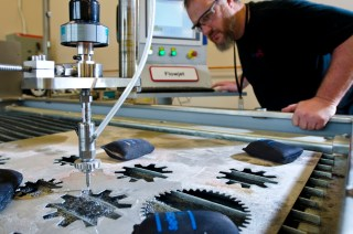 A TechShop maker cuts metal on a flowjet in the Detroit facility.