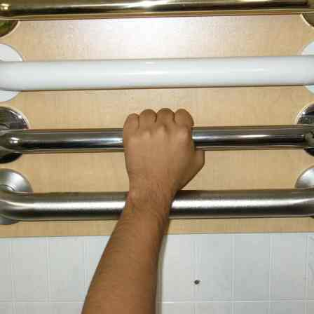 Hand grabbing a row of shower bars in four different metal finishes.