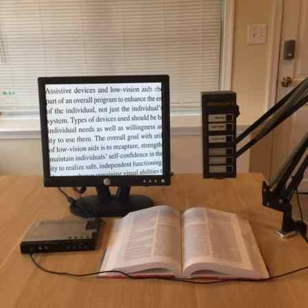 Computer monitor displays magnified text from the open book in front of it. A Video Eye camera is positioned to the side.