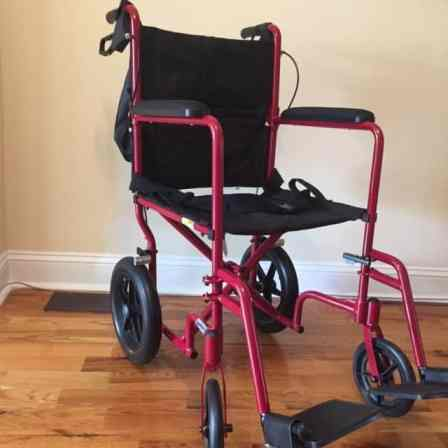 Transport wheelchair with a red metal frame.