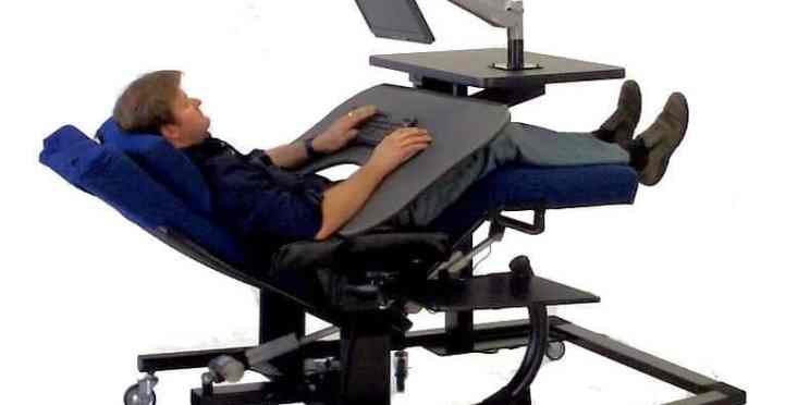 Person in a recliner uses a slanted desk on a rolling mount.