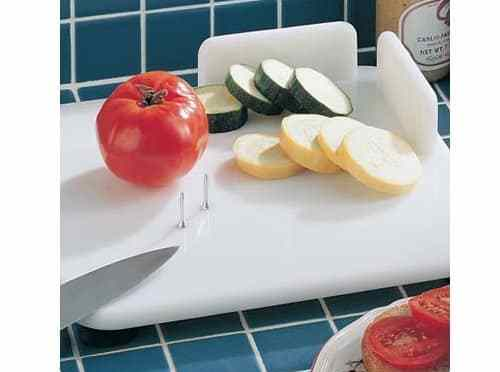 Sliced vegetables on a white cutting board with raised edge guard and metal pins.