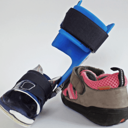 Foot brace leaning against a child's sneaker