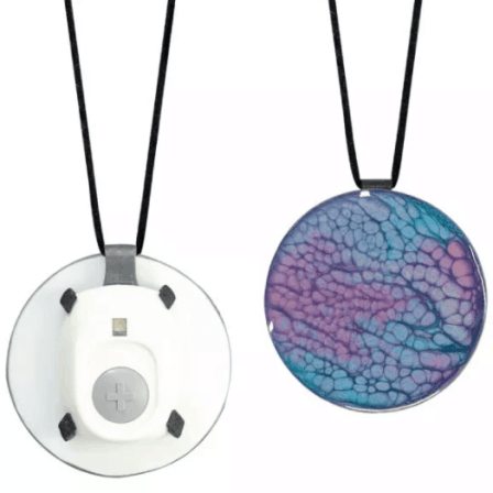 Medical alert button affixed to the back of a decorative blue disk on a necklace.