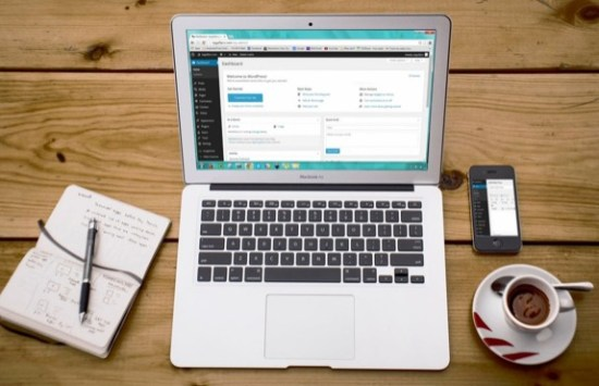 Blogging. A laptop pictured on a wooden table with a notebook, phone and coffee around.it