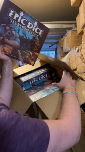 A member of Golden Bell Games in a Garage Holding a copy of Epic Dice