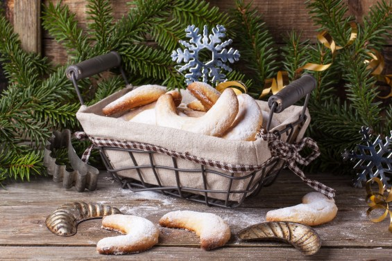 Homemade sugar cookies crescent served in basket with vintage cookie-cutters near christmas tree over old wooden table