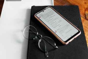 mobile phone and eyeglasses on top of a planner