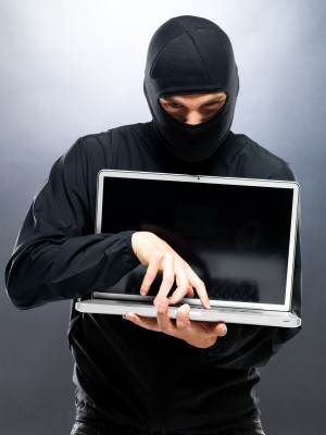 Man dressed as a thief with a laptop