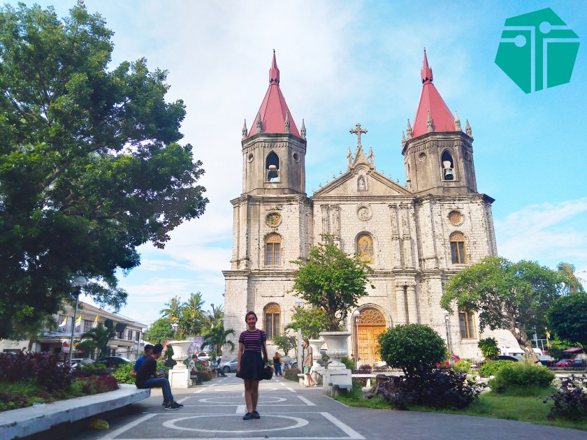 A photo of a lady standing with the Molo Church behind. This Photo was taken during our Capture Capiz and Iloilo Tour.