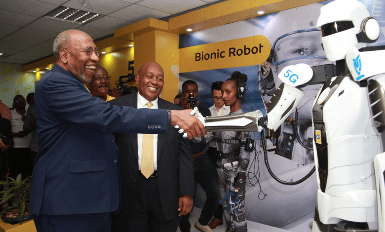 Uganda's Prime Minister Ruhakana Rugunda(L) shakes hands with a robot that uses the 5G network during the 5G technology trial ceremony in Kampala, Capital of Uganda, Jan. 17, 2020