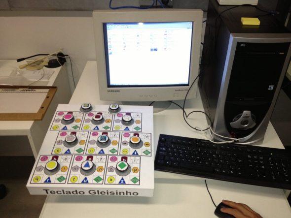 Painel com onze botoeiras coloridas, tipo cogumelo, diante de um computador desktop com monitor de tubo.