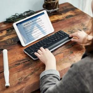 mulher utiliando a linha braille conectada a um tablet