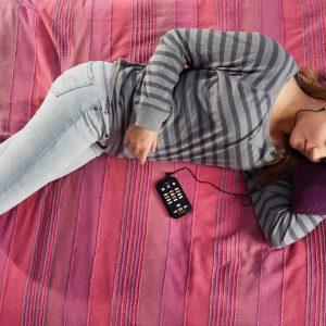 Jovem deitada na cama com forne de ouvido e o Victor Reader Stream