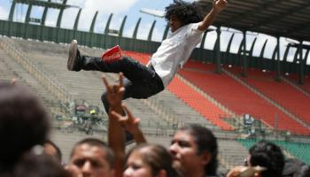 young latino man crowdsurfing high in the air