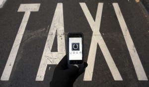 The logo of car-sharing service app Uber on a smartphone over a reserved lane for taxis in a street is seen in this photo illustration taken in Madrid on December 10, 2014. REUTERS/Sergio Perez  (SPAIN) - RTR4HGT3
