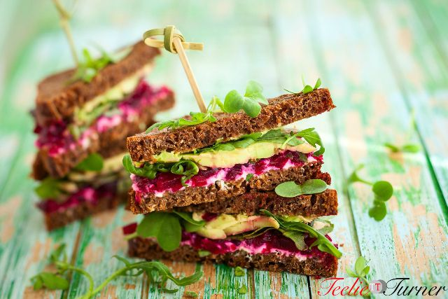 sandwich with beet,cheese,avocado and arugula