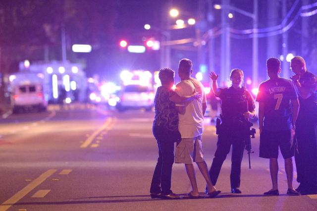 Orlando police officers direct family members away from a shooting at a nightclub in Orlando, Fla., Sunday.