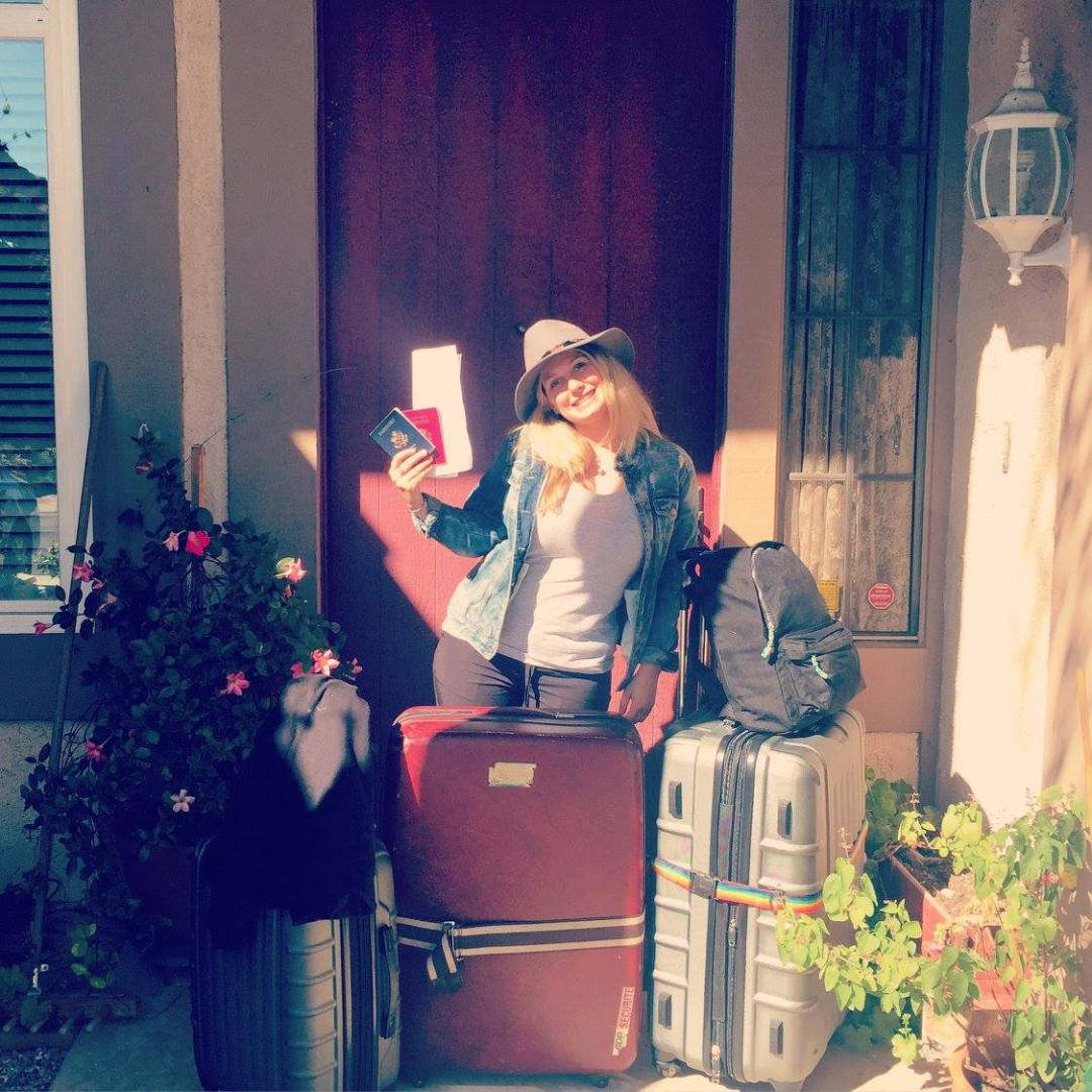 Anna smiling before her trip to Barcelona, Spain, standing outside her house with her suitcases and passport.