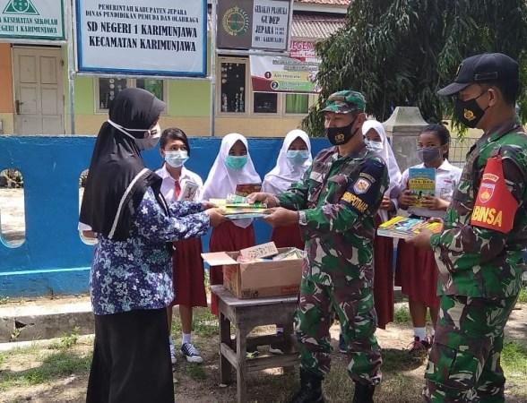 Babinpotmar pos TNI AL dan Babinsa Koramil Karimunjawa menyerahkan buku ke SD