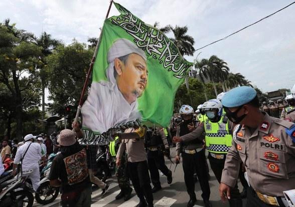 Para pendukung Muhammad Rizieq Shihab, Pimpinan Front Pembela Islam (FPI), sambil membawa bendera besar bergambar ulama kontroversial itu melakukan unjuk rasa di Jakarta 18 Desember 2020.
