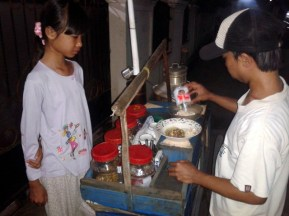 My daughter, waiting for sekoteng seller (special warm beverages from indonesia), makes her order