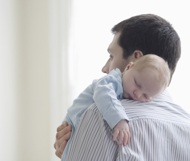 Newborn Baby Sleeping On Fathers Shoulder At Home