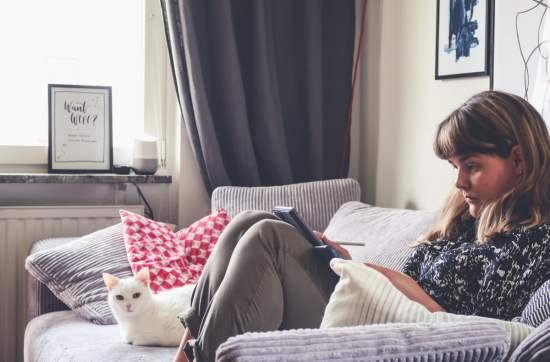 Elin sitter i soffan och läser på en iPad, bredvid ligger hennes vita katt Klara