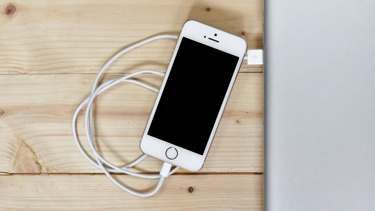 Celular de la marca apple conectado a una laptop