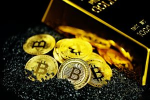 A pile of Bitcoins on black crystals next to a gold bullion