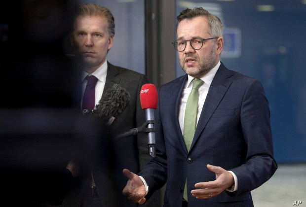 FILE - German Minister of State for European Affairs Michael Roth, right, speaks with the media as he arrives at the Europa building in Brussels, Dec. 11, 2018.