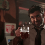 a screencap of mr. clark (played by gabe khouth) with a beer