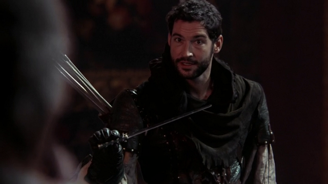 a screencap of robin hood (played by tom ellis) stealing a magic wand from rumpelstiltskin