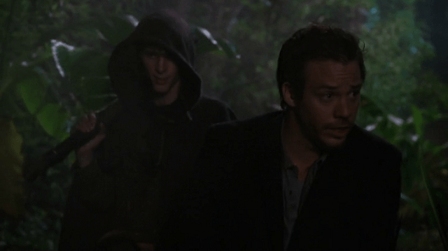 a screencap of felix (played by parker croft) and neal (played by michael raymond james) walking through the woods