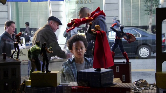 a screencap of a little kid looking at some avengers action figures