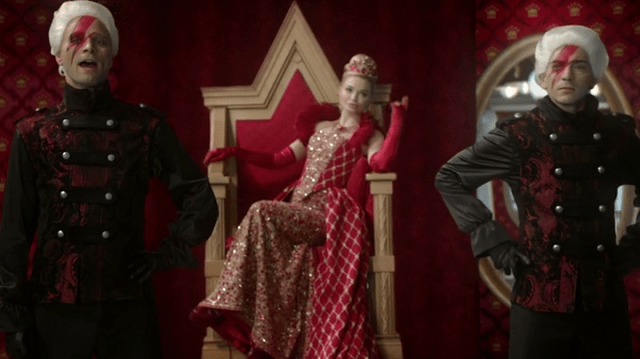 a screencap of the red queen (played by emma rigby) flanked by tweedledee and tweedledum (played by matty finochio and ben cotton) the tweedles have ziggy stardust makeup on their faces