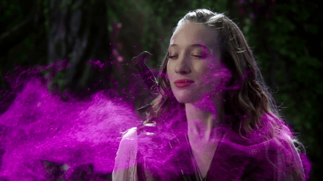 a screencap of alice (played by sophie lowe) inhaling some purple mist