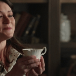 a screencap of belle (played by emilie de ravin) holding up chip