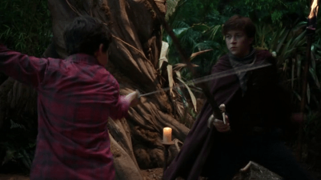 a screencap of henry (played by jared s. gilmore) swordfighting with lost boy devin (played by skyler gisondo)