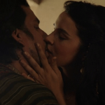 a screencap of jafar (played by naveen andrews) kissing amara (played by zuliekha robinson)