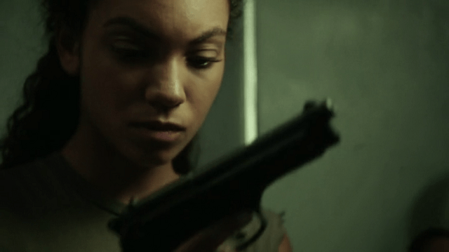 a screencap of jenny mills (played by lyndie greenwood) holding a gun