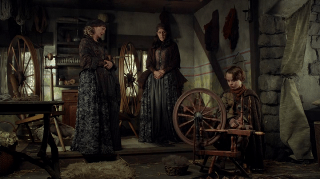 a screencap of the spinsters (played by lindsay collins and glynis davies) teaching a young rumpelstiltskin (played by wyatt oleff) to use a spinning wheel