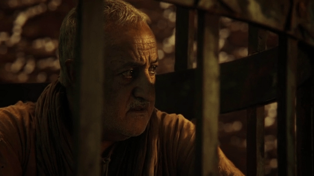 a scrreencap of the old prisoner (played by brian george) in a cage