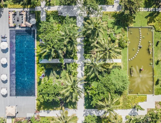 Aerial view of the Sofitel Luang Prabang Laos, including a view of their beautiful lush botanical gardens and sparling amethyst-tonedpool.