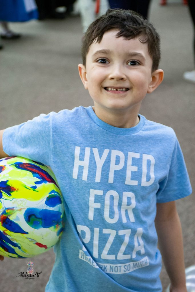 young boy smiling while holding a balloon